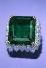 Chalk Emerald. Rectangular step-cut medium-to-dark slightly blue green beryl (var. emerald) (37.8 ct) in a ring. Lot described as