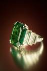 Maximillian Emerald. Modified rectangular step-cut medium-to-dark blue green beryl (var. emerald) (21.04 ct) in a ring. Lot described as