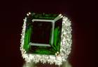 Chalk Emerald. Rectangular step-cut medium-to-dark slightly blue green beryl (var. emerald) (37.8 ct) in a ring. Lot described as