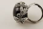 Oval cabochon-cut very dark blue gray corundum (var. star sapphire) (70.79 ct) in a ring. Lot described as