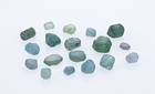 These natural sapphire crystals from the Missouri River deposit in Montana exhibit the varying colors of greens to blues. The crystals have been eroded from the host rock and weathered by water and wind, exhibiting a tumbled worn appearance.