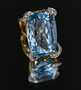 "This ring has a very large 52-carat aquamarine of amazing blue color. It is set in a most unusual and unique yellow gold mounting; the prongs ""float"" up over the corners of the gem in a ribbon-like motif. Accenting the central aquamarine are round brilliant cut diamonds that are bead set in the ""ribbon"" prongs. The date of the ring is unknown, but it appears to be a custom made, one-of-kind piece."
