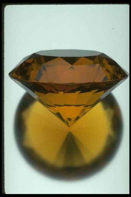 Photograph of a round brilliant-cut citrine (NMNH G3732) from the National Gem Collection with reflection