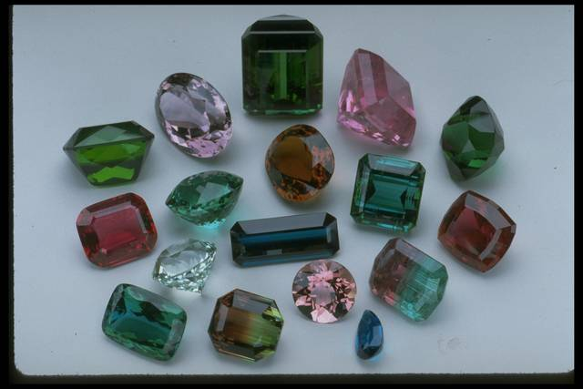 Photograph of a group of faceted elbaites from the National Gem Collection displaying a range of colors from different localities.