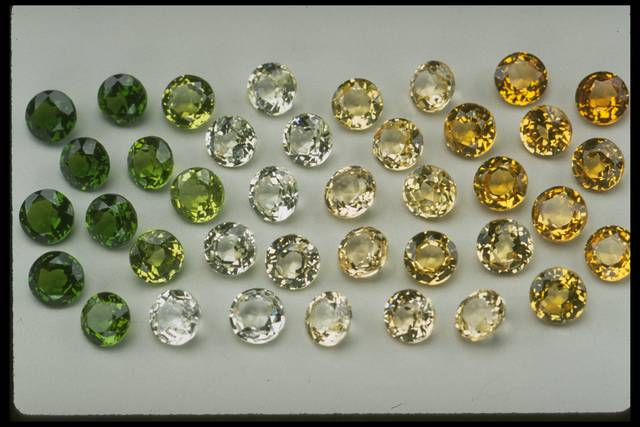 Photograph of a group of half-carat grossular garnets (NMNH G7918) from the National Gem Collection displaying a range of colors