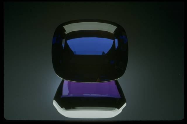 Photograph of a tanzanite (NMNH G4876) from the National Gem Collection that displays blue-to-purple pleochroism. In this photo, the crystal is blue but the reflection is purple.