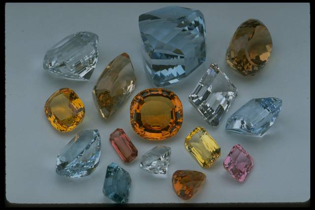 Photograph of a group of topaz gems from the National Gem Collection displaying a range of colors