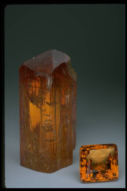 Photograph of the uncut Imperial topaz (NMNH 116879) and a faceted Imperial topaz (NMNH G3401) from the National Gem and Mineral Collection