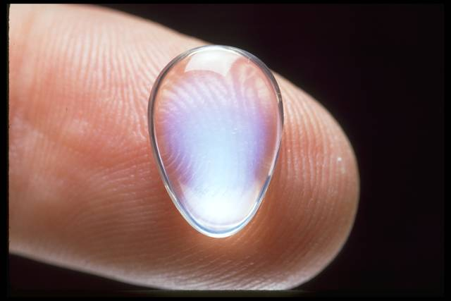 Photograph of a teardrop-shaped moonstone (NMNH G8821) from the National Gem Collection placed on a fingertip