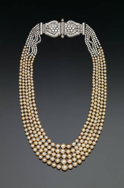 G6757 (Dunn Pearl Necklace) was donated by Mrs. Arthur Wallace Dunn in 1977. Designed by Cartier, Inc. There are 339 natural pearls that range in size from 3.3mm to 7.8mm that are a cream color and well matched.  The platinum clasp is a beautiful example of the Art Deco era and has six diamond chains on each side that attach to the pearls.  There are 428 old mine cut diamonds in the clasp and chains combined that have a total weight of approximately 16 carats.