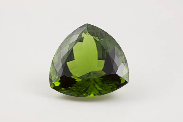 Trillion-cut green forsterite (var. peridot) weighing 100.15 ct.