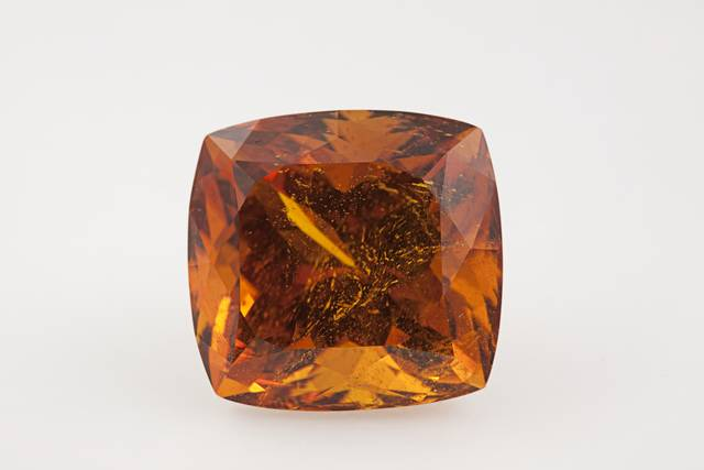 Square cushion-cut orange clinohumite weighing 21.39 ct.