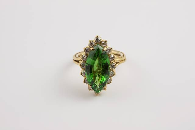 Marquise-shaped step-cut medium-to-dark green grossular (var. garnet (tsavorite)) (7.08 ct) in a ring with 16 small round diamonds, set in yellow gold.