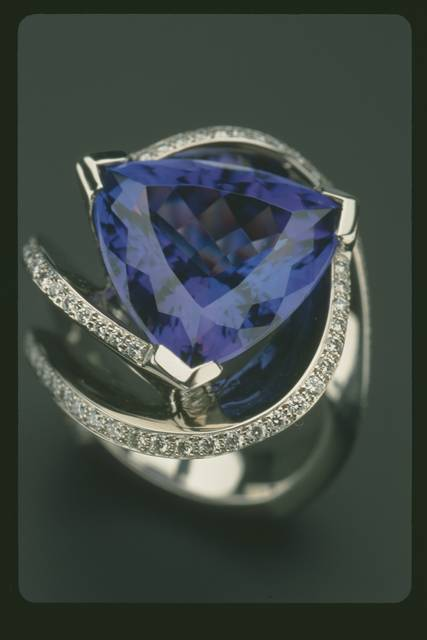 Schneider Tanzanite Ring. Trillion-cut dark violet blue zoisite (var. tanzanite) (12.11 ct) set in platinum with 1.89 ct tl wt round diamonds.