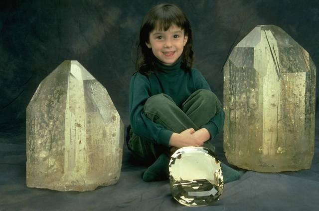 Photograph of Jessica Clark with two uncut topaz crystals (148089 and 148090) and a large faceted topaz (NMNH G9875).