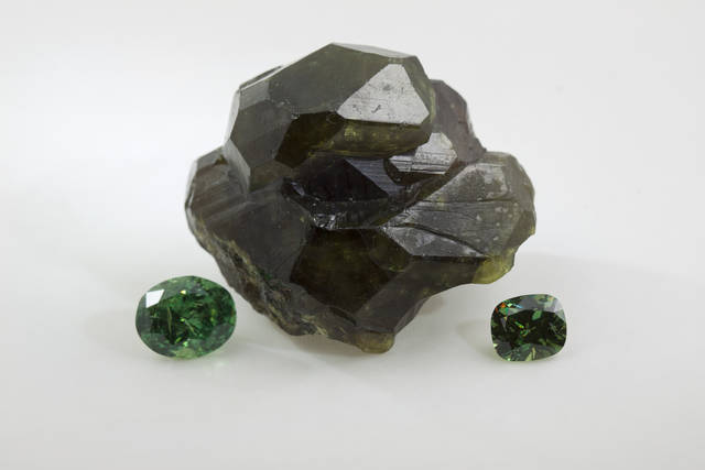 Rough crystal and two faceted gems: 6.96ct oval and 3.00ct cushion cut demantoids.