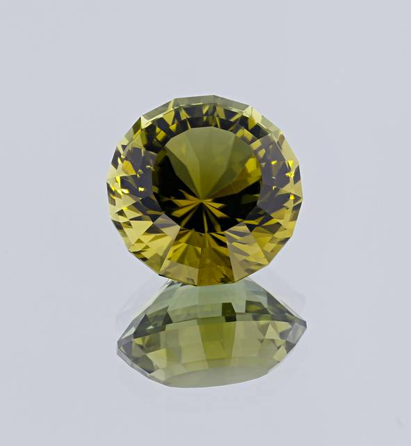 This fancy round-cut tourmaline, faceted by Paul Merkel, is from Mozambique and has an unusual yellowish-green color