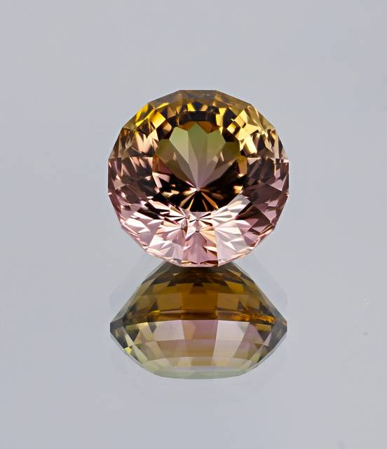 This fancy round-cut tourmaline is from Nigeria, exhibiting a golden-yellow to purplish-pink bi-color.