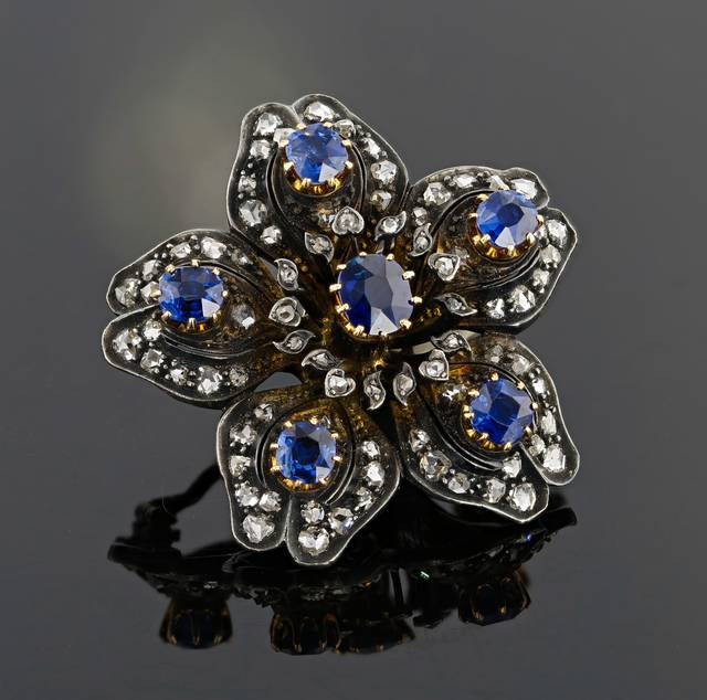The brooch, believed to have been made in England in the 1880s, is made of silver and gold as commonly seen in late Victorian era jewelry (1837-1901). The sapphires are an intense beautiful blue color, and due to the type of inclusions present, they are most likely from Cambodia.
