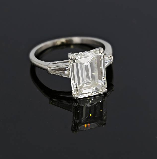 "The ring features an emerald-cut diamond that weighs 4.58 carats, flanked by two tapered baguette-cut diamonds. It has a square or rectangular outline with rectilinear facets arranged parallel to the girdle of the stone, with truncated corners creating an octagonal outline. The facets are arranged in a step-like fashion and produce a ""hall of mirrors"" effect within the diamond."