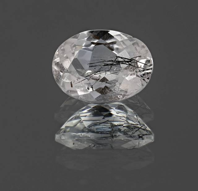This colorless oval topaz from Brazil has needle-like inclusions of the mineral columbite. Columbite is a heavy oxide mineral that is an ore of niobium and tantalum.