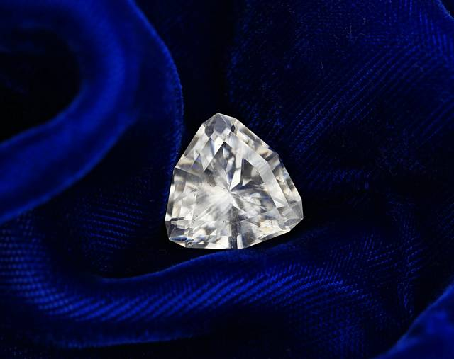 It is unusual to see a faceted dolomite. This gem has a traingular cut and is colorless with a light brown tone.
