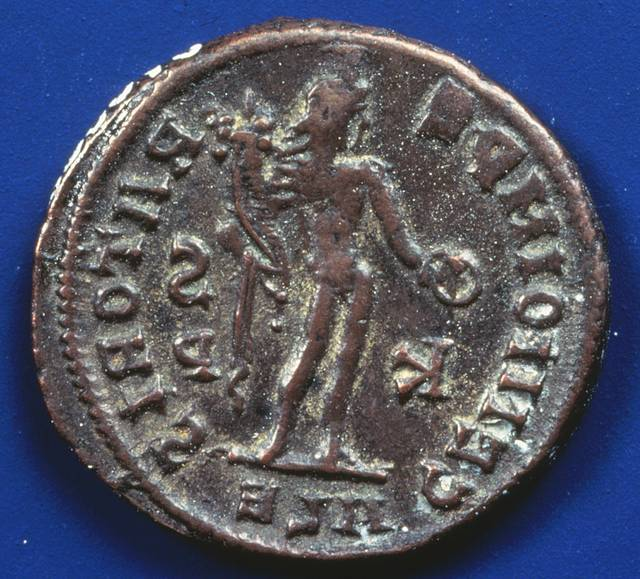 Image: a coin with some writing and a figure in silhouette.